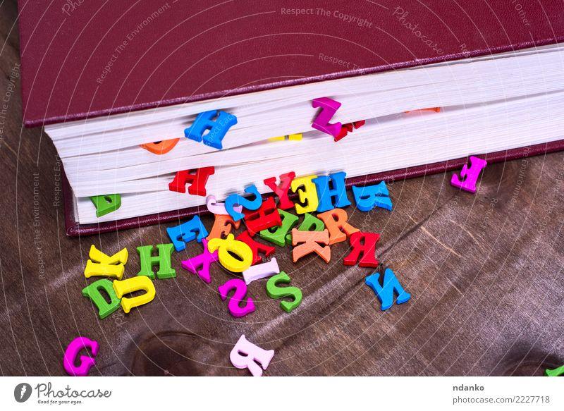 mehrfarbige Buchstaben des englischen Alphabets blau rot Holz braun rosa Tisch lernen Information