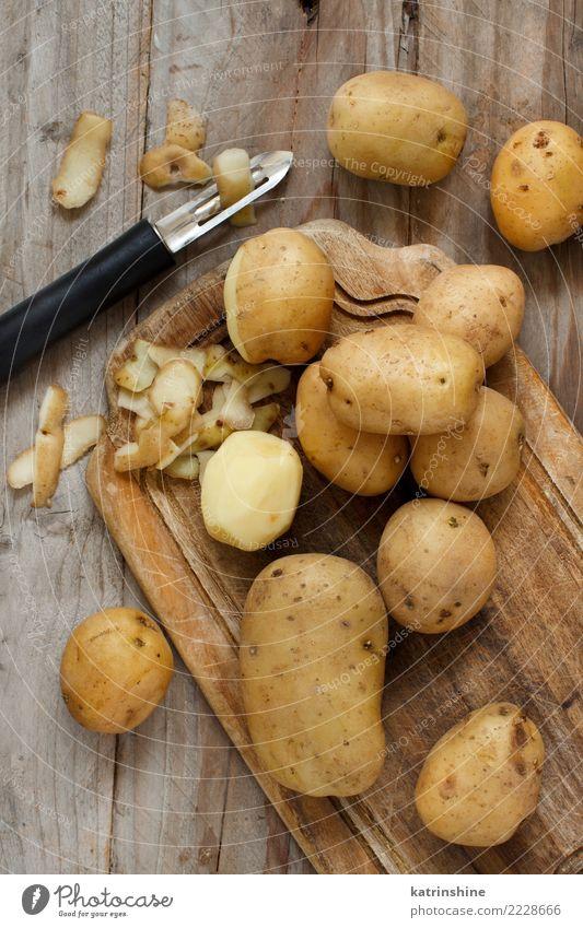 Rohe Kartoffeln mit einer Draufsicht des Gemüseschälers Lebensmittel Ernährung Vegetarische Ernährung Haut Menschengruppe Holz frisch braun Ackerbau