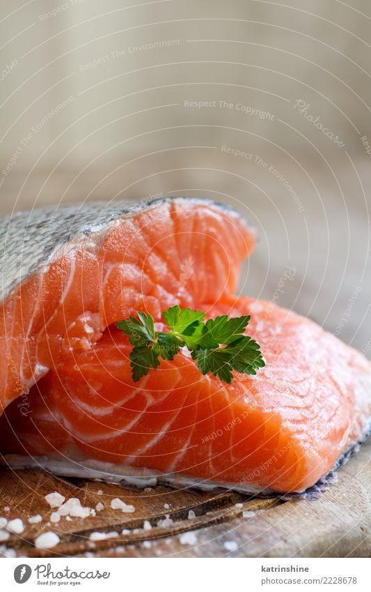 Frische rohe Lachse auf einem hölzernen Schneidebrett Meeresfrüchte Kräuter & Gewürze Ernährung Essen Abendessen Diät Tisch frisch grün rot Hintergrund
