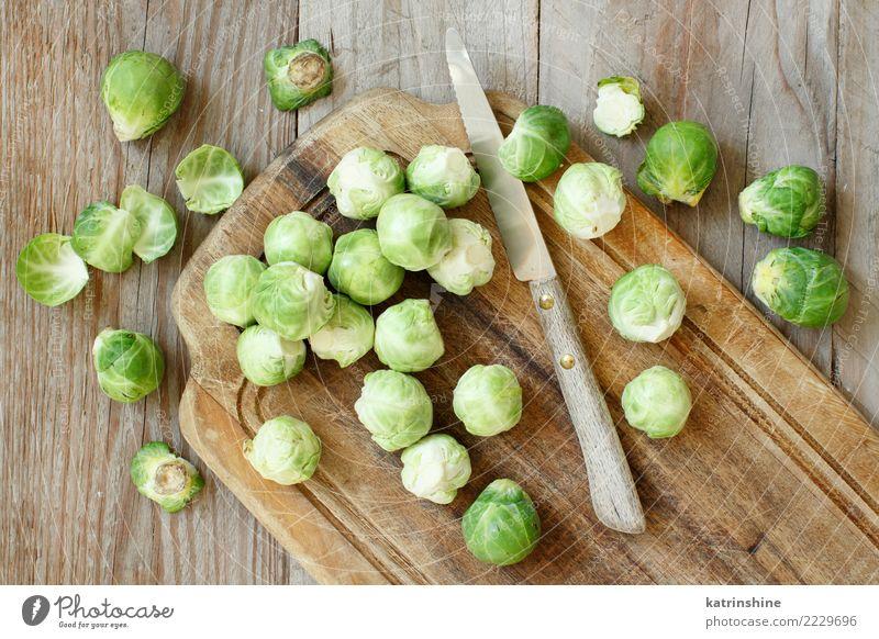 Rosenkohl auf einem hölzernen Brett mit einem Messer Gemüse Ernährung Vegetarische Ernährung Diät Tisch Gastronomie frisch hell natürlich retro braun grün