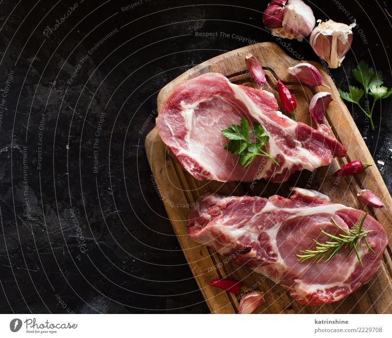 Rohe Schweinefleischsteaks nannten capicola mit Gemüse und Kräutern Fleisch Kräuter & Gewürze Ernährung Abendessen frisch oben grün rot Capicolla Holzplatte