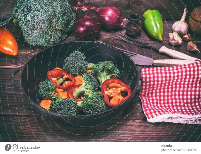 Gemüse in einer schwarzen runden Pfanne Ernährung Essen Vegetarische Ernährung Diät Gabel Tisch Küche Natur Pflanze Holz frisch natürlich braun grün rot