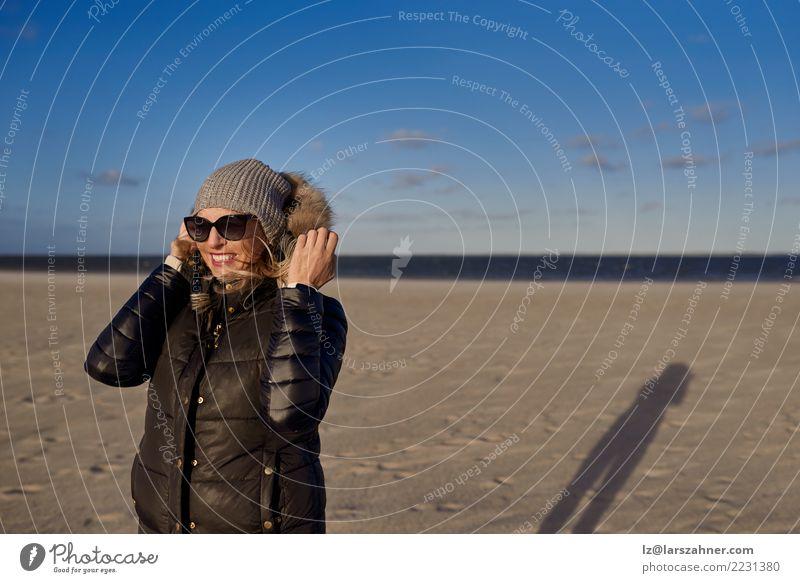 Modische Frau, die auf einem Strand bei Sonnenuntergang steht Mensch Natur Ferien & Urlaub & Reisen Landschaft Meer Erwachsene Lifestyle Herbst Küste Glück