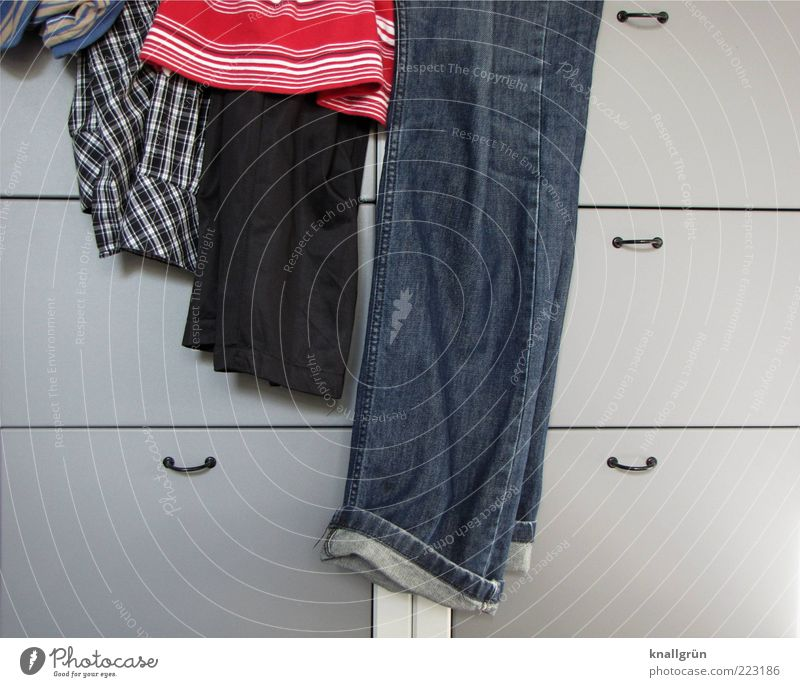 Der Mann im Haus blau rot grau Mode Ordnung liegen modern Bekleidung Häusliches Leben T-Shirt Jeanshose Hemd Hose hängen trendy gestreift