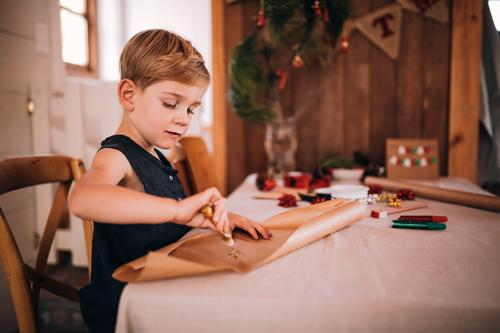 Kleinkindjunge, der zu Hause Weihnachtskarten und -geschenke in Handarbeit macht Freude Glück Winter Weihnachten & Advent Kind Junge Schreibstift niedlich Farbe