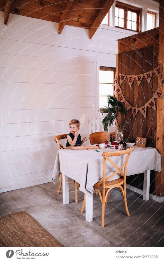 Netter kleiner Junge, der Weihnachtssüßigkeit isst und Geschenke einwickelt Essen Winter Tisch Wohnzimmer Kind Kindheit Hütte sitzen Weihnachten Süßigkeiten