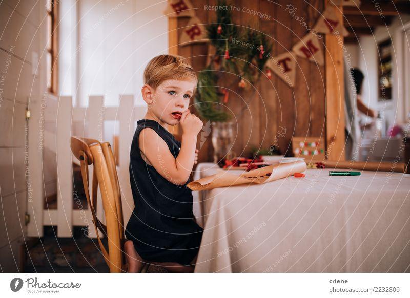Kaukasisches kleines Kleinkind, das Weihnachtssüßigkeit isst Essen Winter Tisch Wohnzimmer Weihnachten & Advent Kind Junge 1-3 Jahre 3-8 Jahre Kindheit