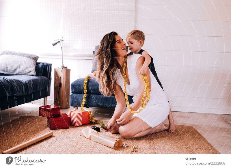 Mutter- und Kleinkindsohn, der zusammen Weihnachtsgeschenke einwickelt Freude Glück Winter Wohnzimmer Weihnachten & Advent Kind Mensch Eltern Erwachsene 2