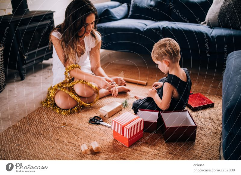 Junge Familie, die zu Hause Weihnachtsgeschenke einwickelt Freude Glück Winter Wohnzimmer Weihnachten & Advent Kindererziehung Handwerk Kleinkind Eltern