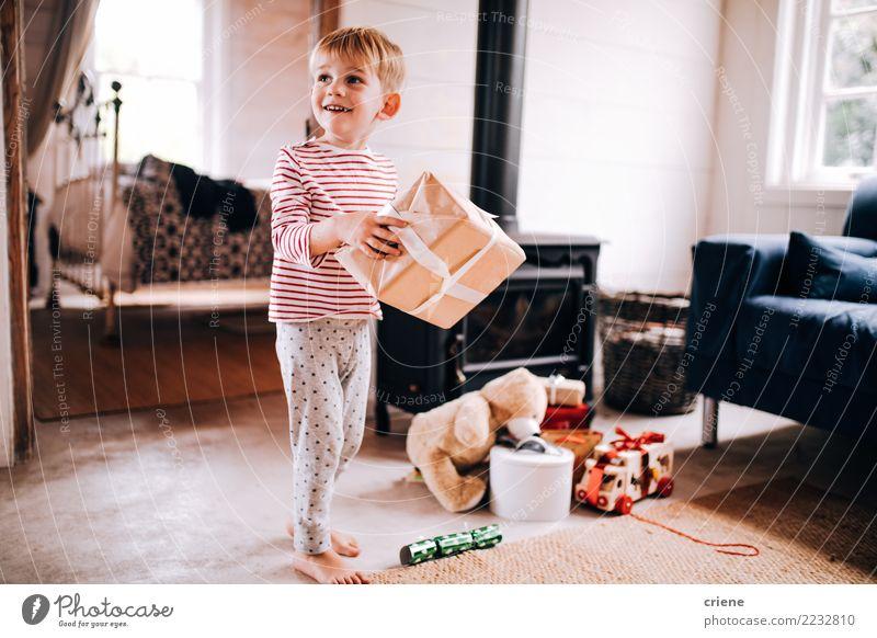 Aufgeregter kleiner Junge mit Weihnachtsgeschenken zu Hause Freude Glück Kind Kleinkind Kindheit 1 Mensch 1-3 Jahre 3-8 Jahre Spielzeug Lächeln lachen niedlich
