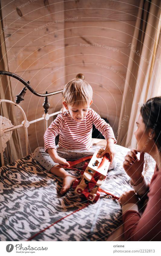 Llittle-Junge, der auf Bettöffnungs-Weihnachtsgeschenken mit Mutter sitzt Kind Frau Mensch Jugendliche Weihnachten & Advent Haus Freude Winter Erwachsene Liebe