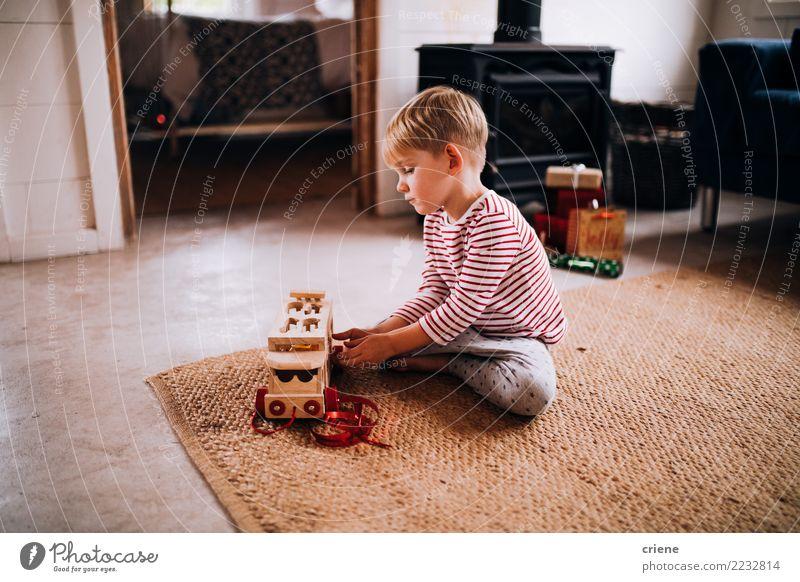 Kleinkindjunge, der mit tragenden Pyjamas des neuen Spielzeugs spielt Lifestyle Freude Glück Freizeit & Hobby Spielen Winter Haus Wohnzimmer