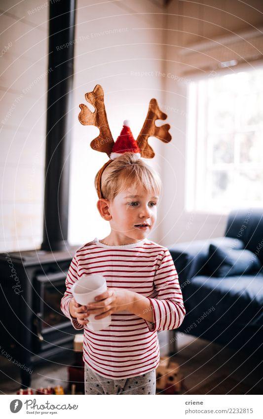 Tragendes Renohrskostüm des netten Kleinkindes am Weihnachtstag trinken Lifestyle Freude Glück Winter Haus Wohnzimmer Weihnachten & Advent Kind Wärme Lächeln