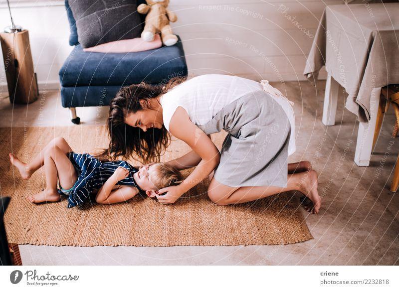 Glückliche Mutter, die zu Hause ihren netten Kleinkindsohn kitzelt Lifestyle Freude Spielen Wohnzimmer Küche Kind Mensch Eltern Erwachsene Lächeln lachen Liebe
