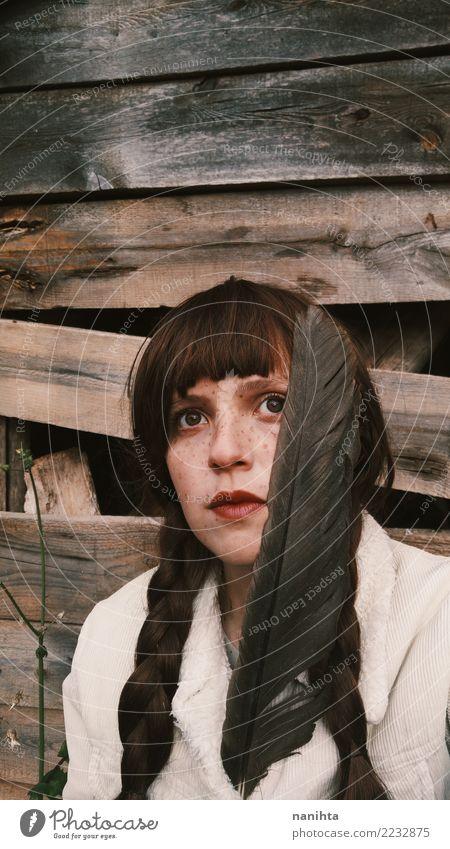 Junge Frau, die weg schaut, eine Feder halten exotisch schön Haut Gesicht Sommersprossen Mensch feminin Jugendliche 1 18-30 Jahre Erwachsene Jacke