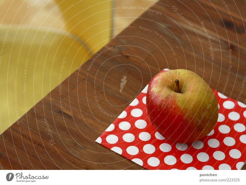 Ein Boskop Apfel liegt auf einem Tisch vor dem ein gelber Vintage Stuhl steht. Gesunde Ernährung, Obst Lebensmittel Gesundheit Dekoration & Verzierung Kitsch