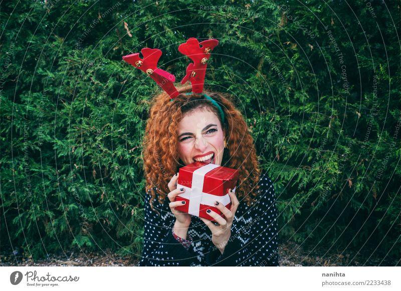Junge Frau, die ein Weihnachtsgeschenk isst Mensch Natur Jugendliche Weihnachten & Advent Pflanze schön grün Baum rot Freude Winter 18-30 Jahre Erwachsene Leben