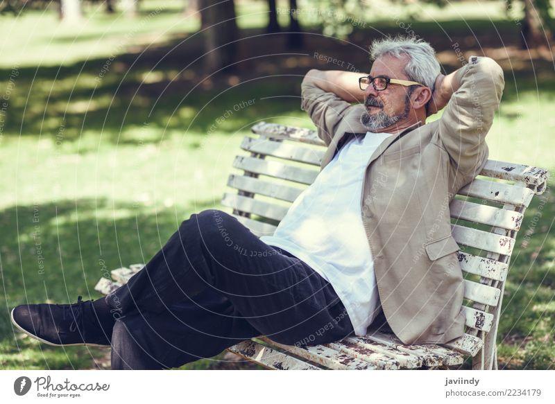 Nachdenklicher reifer Mann, der auf einer Bank in einem städtischen Park sitzt. Mensch alt Erwachsene Straße Lifestyle Senior Glück maskulin 45-60 Jahre