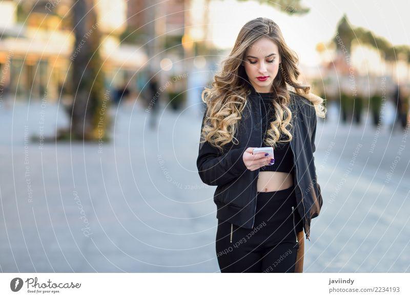 Frau, die mit ihrem intelligenten Telefon im städtischen Hintergrund simst Lifestyle Stil schön Haare & Frisuren PDA Mensch feminin Junge Frau Jugendliche