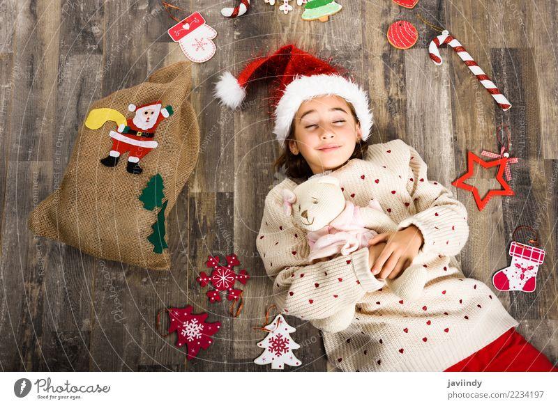 Kleines Mädchen, das den Sankt-Hut schläft auf Bretterboden trägt Glück schön Dekoration & Verzierung Weihnachten & Advent Kind Frau Erwachsene Kindheit 1