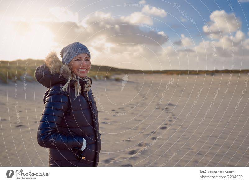 Modische Frau, die auf einem Strand bei Sonnenuntergang steht Mensch Natur Ferien & Urlaub & Reisen Landschaft Meer Gesicht Erwachsene Lifestyle Herbst Küste