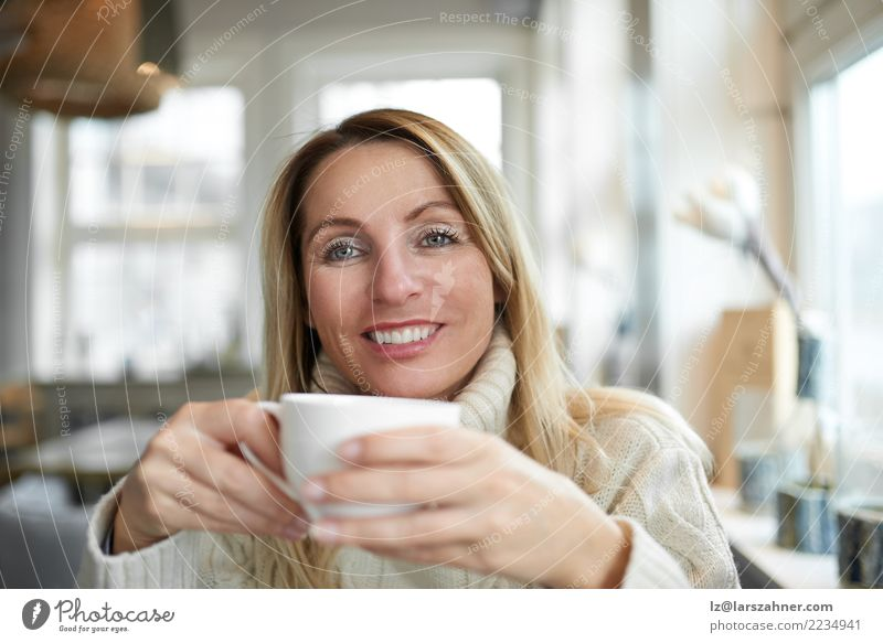 Schönheit, die sich zu Hause mit Kaffee entspannt Getränk trinken Tee Glück Gesicht ruhig Wohnzimmer Frau Erwachsene 1 Mensch 30-45 Jahre blond Lächeln
