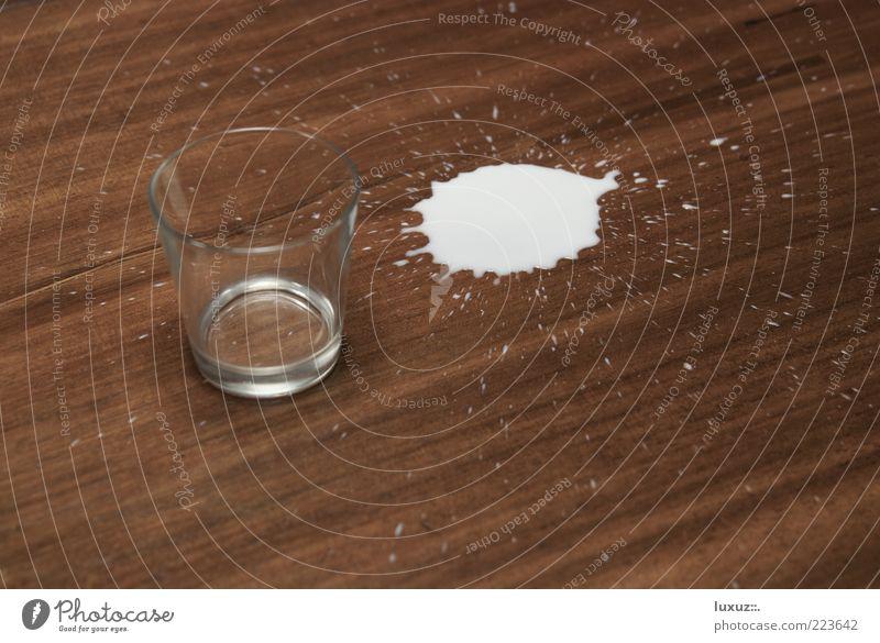 Halb voll oder halb leer? Milch klecksen Glas Tropfen verschütten tollpatschig Fehler durstig milk Fleck Getränk verlieren Hintergrund neutral Holz Seite