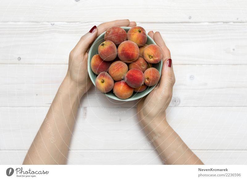Weibliche Hände, die eine Schüssel Pfirsiche halten Lebensmittel Frucht Ernährung Essen Frühstück Mittagessen Abendessen Picknick Bioprodukte
