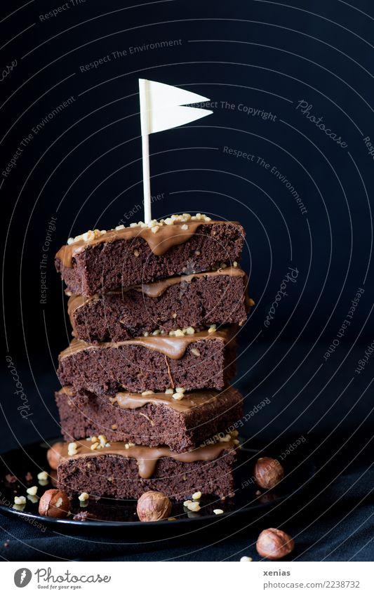 aufgetürmte Stücke Schokoladenkuchen mit Haselnusscreme und weißer Fahne vor dunklem Hintergrund Lebensmittel Kuchen Brownie Creme Nusscreme Krokant Bioprodukte