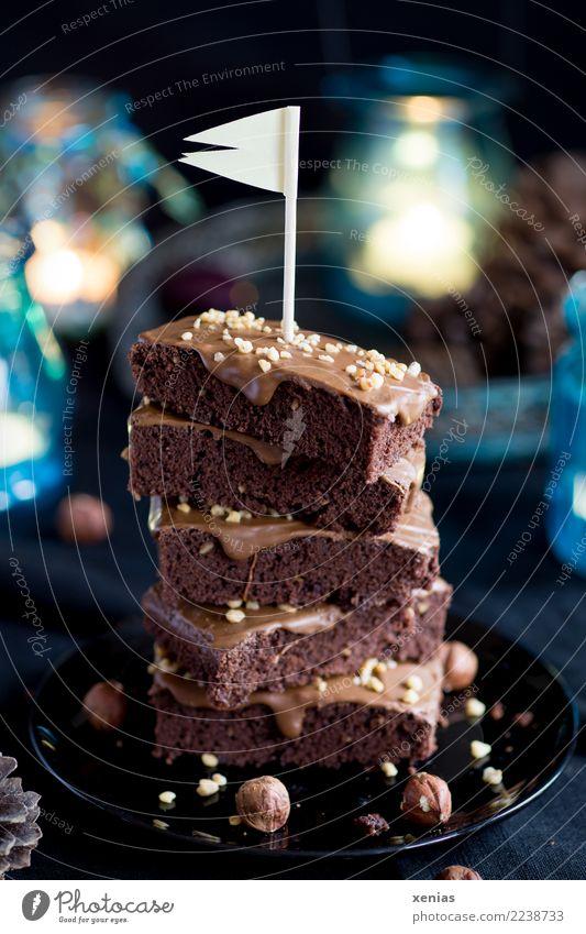 aufgetürmte Schokoküchlein mit Haselnuss und Fähnchen auf schwarzem Teller und blauen Lichtern im Hintergrund Kuchen Schokolade Brownie Schokoladenkuchen