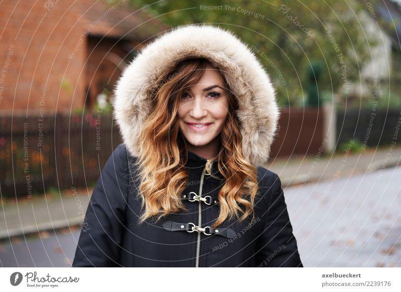 smiling young woman wearing winter coat with fake fur hood Frau Mensch Jugendliche Junge Frau Stadt Winter 18-30 Jahre Erwachsene Straße Lifestyle feminin Stil