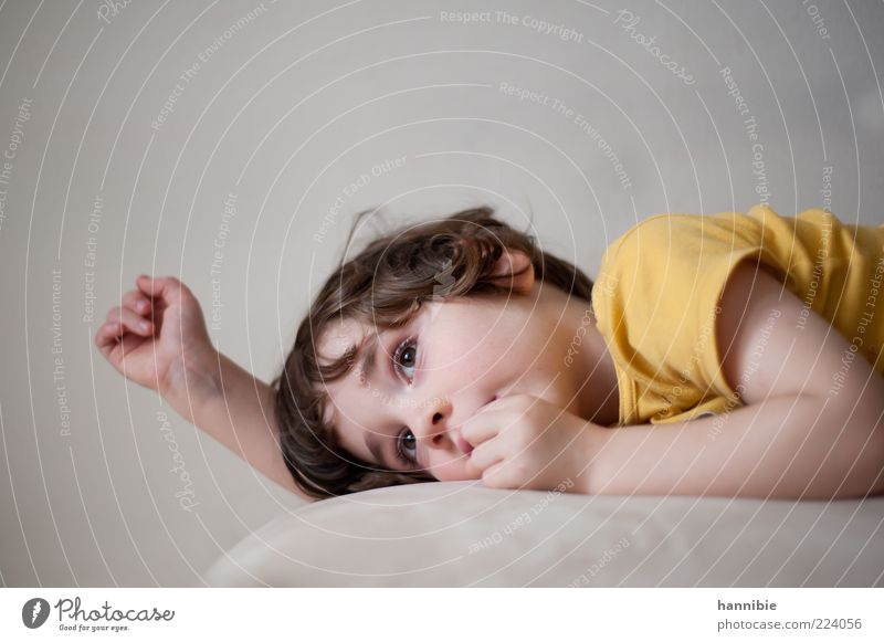 die Ruhe vor dem Sturm Kind Kleinkind Junge Kindheit 1 Mensch T-Shirt brünett gelb grau liegen Blick Langeweile warten planen Erholung Denken verträumt ruhig