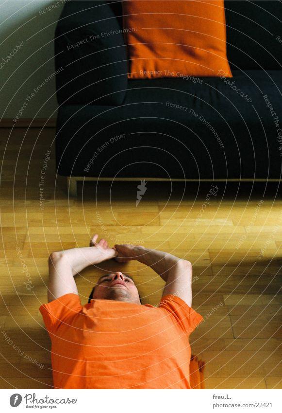 Home-Fitness Mann orange Gesundheit Arme Bodenbelag Sofa sportlich Wohnzimmer Muskulatur Turnen Kissen Parkett unrasiert dehnen