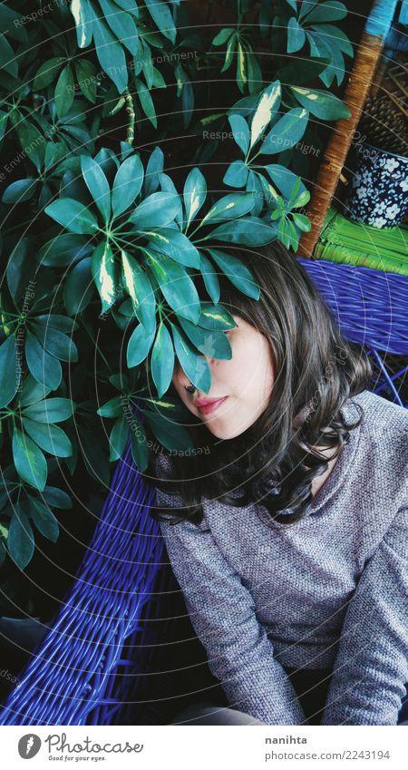 Junge Frau versteckt hinter einer Pflanze Lifestyle Stil exotisch Sinnesorgane Erholung Innenarchitektur Sofa Dachboden Mensch feminin Jugendliche 1 18-30 Jahre