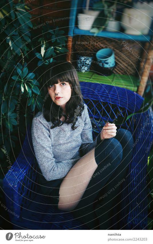 Junge Brunettefrau, die zu Hause sitzt Lifestyle Stil Design schön Innenarchitektur Möbel Sessel Mensch feminin Junge Frau Jugendliche 1 18-30 Jahre Erwachsene
