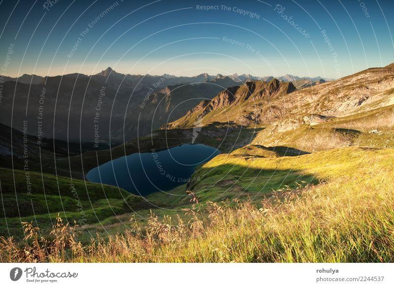 Sonnenaufgang über Alpengipfeln und See im Sommer Berge u. Gebirge Natur Landschaft Himmel Wolkenloser Himmel Sonnenlicht Schönes Wetter Felsen Gipfel blau