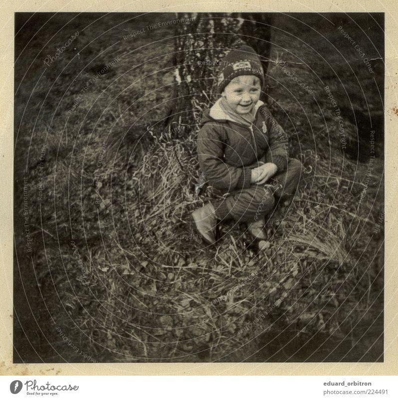 Remember me Kindheit 1 Mensch 3-8 Jahre Baum Gras Hose Jacke Mütze lachen sitzen retro Freude Fröhlichkeit Zufriedenheit Begeisterung Schwarzweißfoto