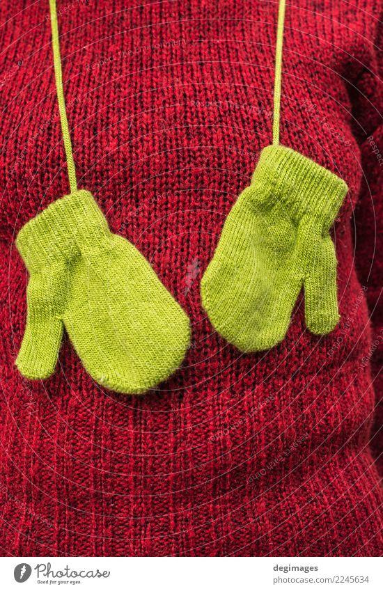 Grüne Handschuhe des Winters auf roter Strickjacke der Frauen Erwachsene Herbst Wärme Mode Bekleidung Pullover Schal Hut natürlich grün Farbe Hintergrund Wolle