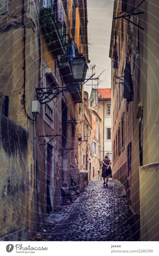 Ältere Dame spaziert durch eine enge Gasse in Lissabon nach Hause Frau gehen Hausfrau Stadt Altstadt Fassaden alt Kopfsteinpflaster Portugal spazieren einsam