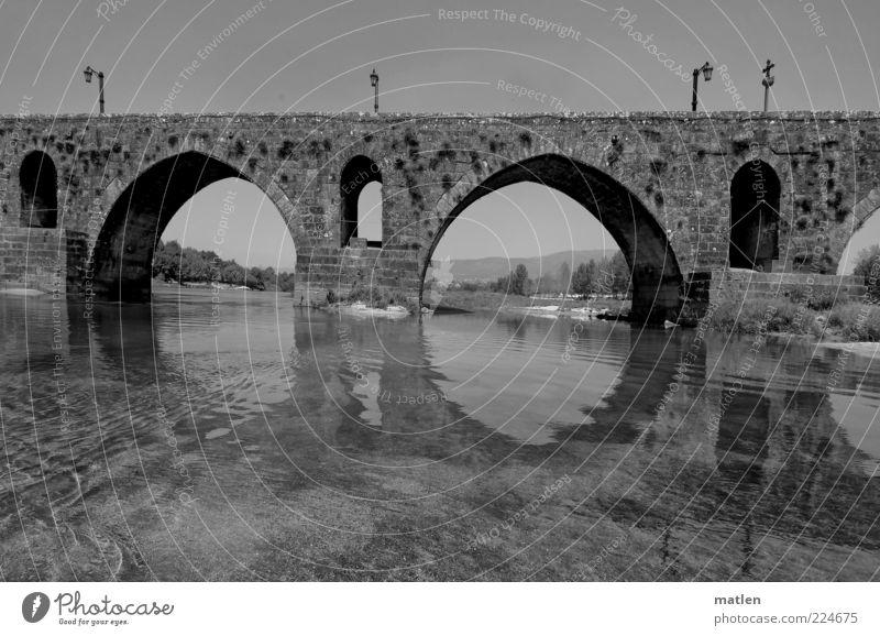 Über.fluss Wasser ruhig Wand Mauer Brücke historisch Fluss Laterne Bogen Wasseroberfläche fließen Kruzifix Übergang Wasserspiegelung Schwarzweißfoto Steinbrücke