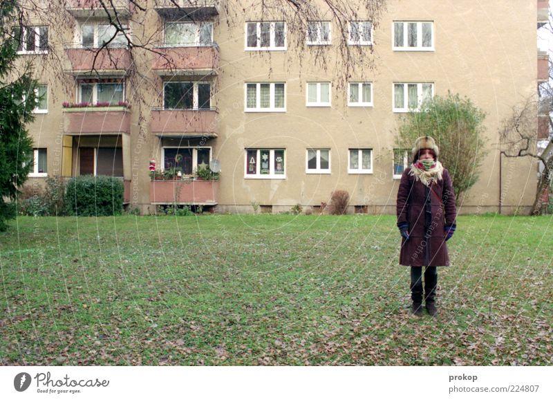 Frau vor Haus Mensch Junge Frau Jugendliche Erwachsene Wiese Fassade Balkon Fenster Bekleidung Hose Mantel Fell Schal Handschuhe Stiefel Mütze stehen warten