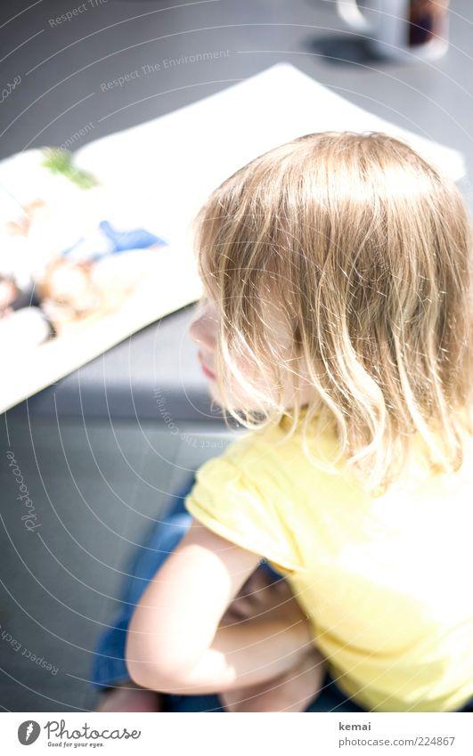 Buch anschauen (II) Mensch Kind Mädchen Kindheit Kopf Haare & Frisuren Nase Arme 1 1-3 Jahre Kleinkind Bilderbuch sitzen glänzend hell klein gelb Farbfoto