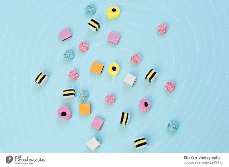 Farbige Süßigkeit zerstreut auf den blauen Hintergrund Weihnachten & Advent Farbe schön Freude gelb Lebensmittel Feste & Feiern Menschengruppe rosa Textfreiraum