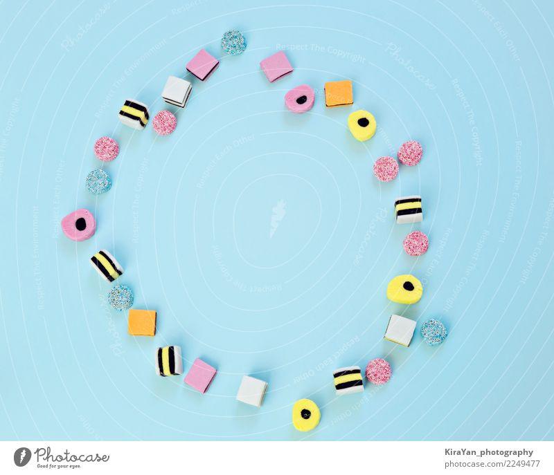 Farbige Süßigkeiten sind auf einem blauen Hintergrund verstreut Farbe rot Freude Essen gelb Kunst Spielen Lebensmittel Feste & Feiern Menschengruppe rosa