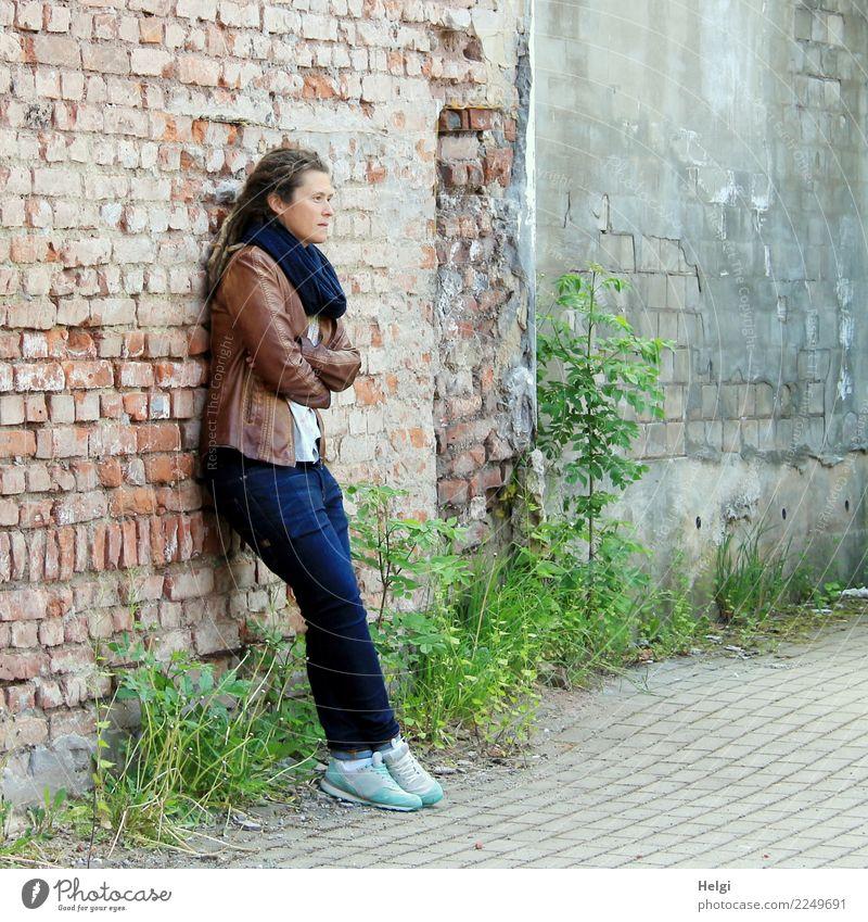 nachdenkliche Frau mit Dreadlocks, in Jeans und brauner Lederjacke steht an einer alten verfallenen Häuserwand Mensch feminin Erwachsene 1 30-45 Jahre Umwelt