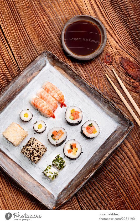 Sushi stellten auf Tonwarenplatte mit Essstäbchen und Sojasoße ein Holz Lebensmittel oben frisch Tisch lecker Tradition Rost Teller Essen zubereiten Mahlzeit