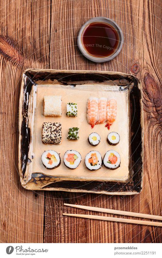 Sushi stellten auf Tonwarenplatte mit Essstäbchen und Sojasoße e Holz Lebensmittel oben frisch Tisch lecker Tradition Rost Teller Essen zubereiten Mahlzeit