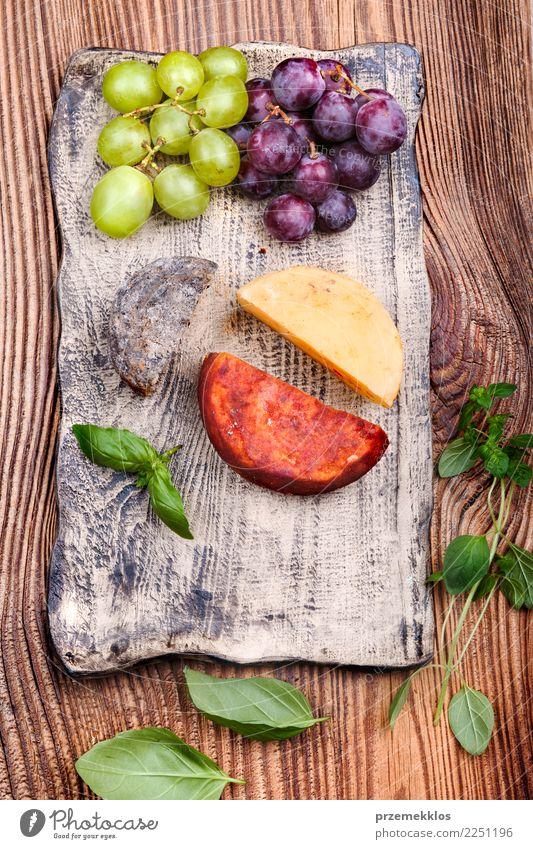 Käse und Trauben, die auf handgemachter Tonwarenplatte verziert werden Lebensmittel Frucht Ernährung Frühstück Mittagessen Teller Tisch Holz Rost frisch lecker