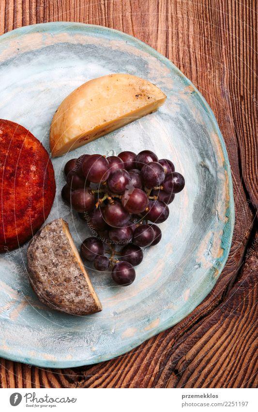 Käse und schwarze Trauben auf handgemachter blauer Tonplatte Lebensmittel Frucht Frühstück Teller Tisch Holz Rost frisch lecker oben Keramik Essen zubereiten