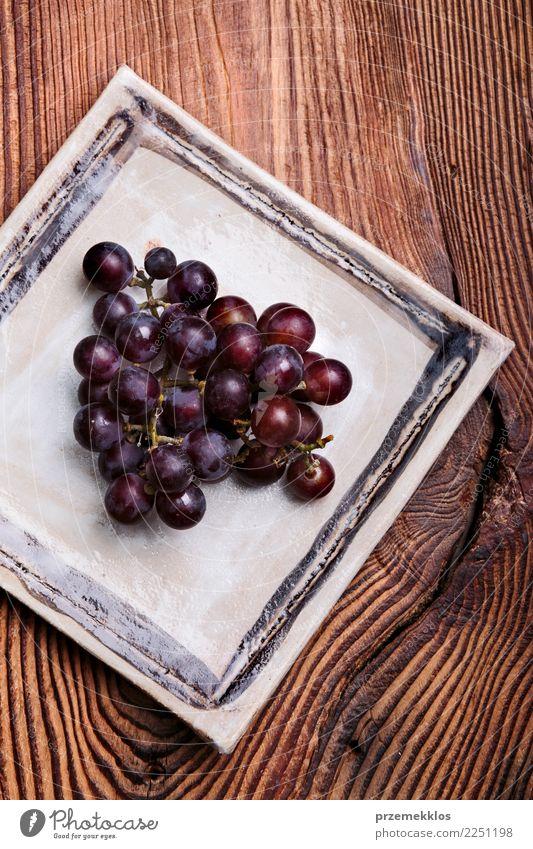 Schwarze Trauben auf handgemachter quadratischer Tonwarenplatte Lebensmittel Frucht Diät Teller Tisch Holz Rost frisch lecker oben Keramik Essen zubereiten